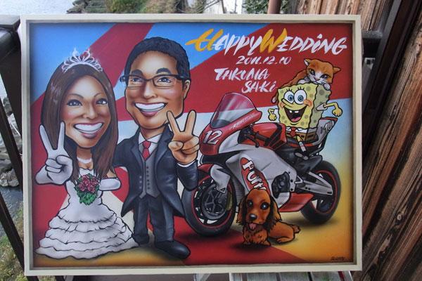 【似顔絵ウェルカムボード バイク】  <p>似顔絵ウェルカムボードのSPサイズとなっています。</p> <p>新郎様が好きなバイクと新婦さまの好きな物が勢揃いの作品となっています。</p>